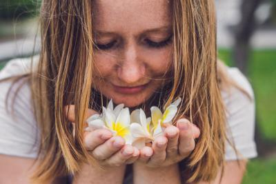 Woman smelling frangipani flowers